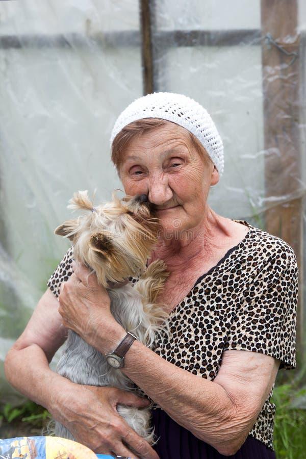 En härlig hög kvinna med hennes hund i en sommarträdgård royaltyfria bilder
