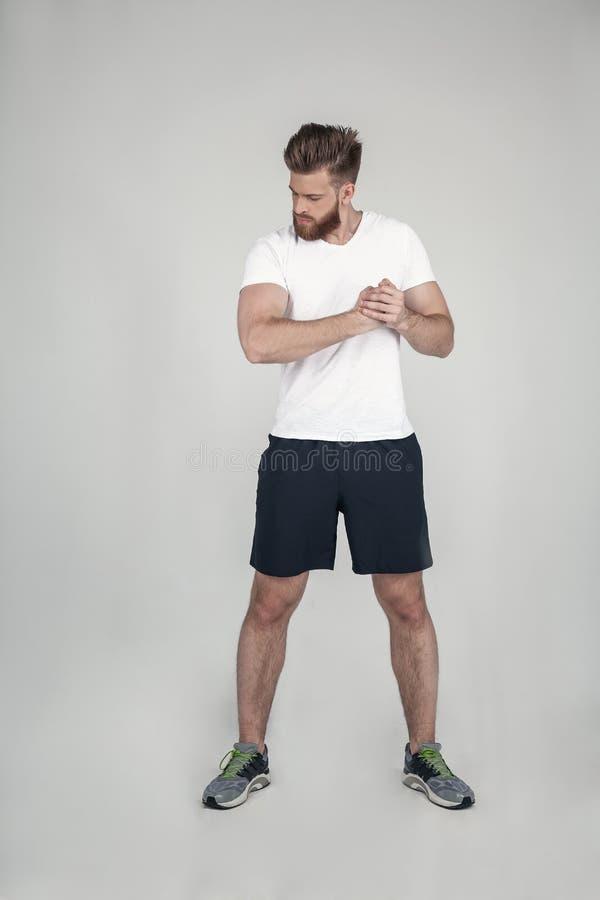 En härlig idrottsman nen med ett skägg visar hans muskler se din biceps iklädda sportkortslutningsgymnastikskor och en vit T-tröj royaltyfri foto