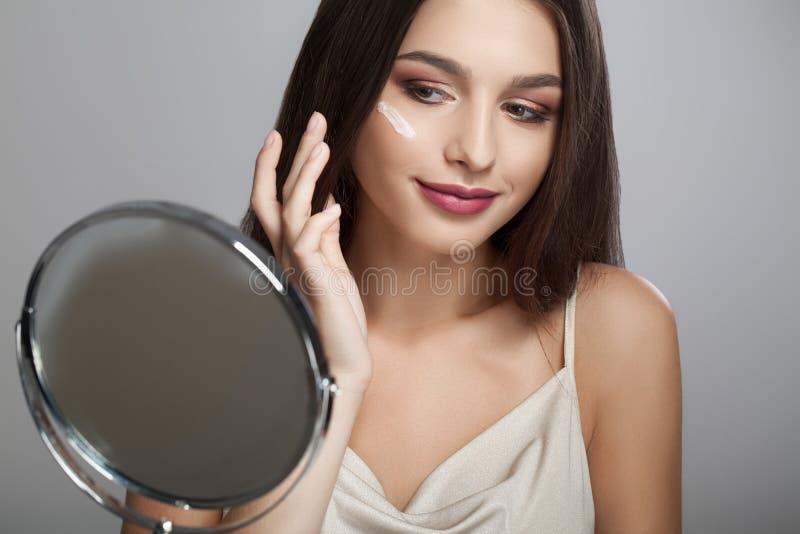 En härlig kvinna asia genom att använda en produkt för hudomsorg, fuktighetsbevarande hudkräm eller royaltyfri bild