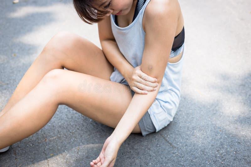 En härlig kvinna får men, sårar, smärtsamt på hennes arm När du charmar den härliga flickan har blåmärket på hennes arm Den nätta royaltyfri bild