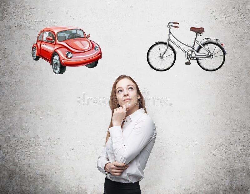 En härlig kvinna försöker valde den mest passande vägen för att resa eller att pendla Två skissar av en bil, och en cykel är dren stock illustrationer