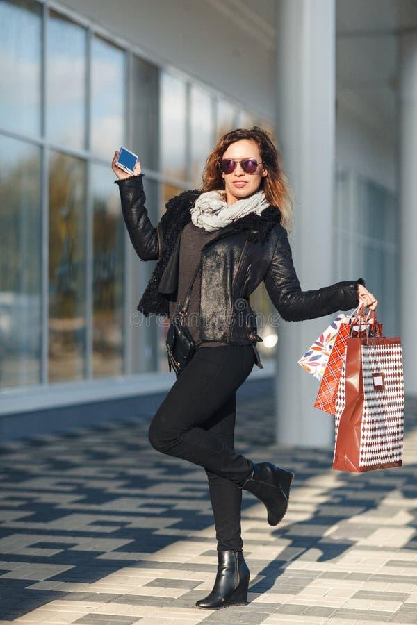 En härlig kvinna går till och med staden på shopping, henne är jätteglad av köp i periodförsäljningarna Begrepp: mode shoppi royaltyfri fotografi