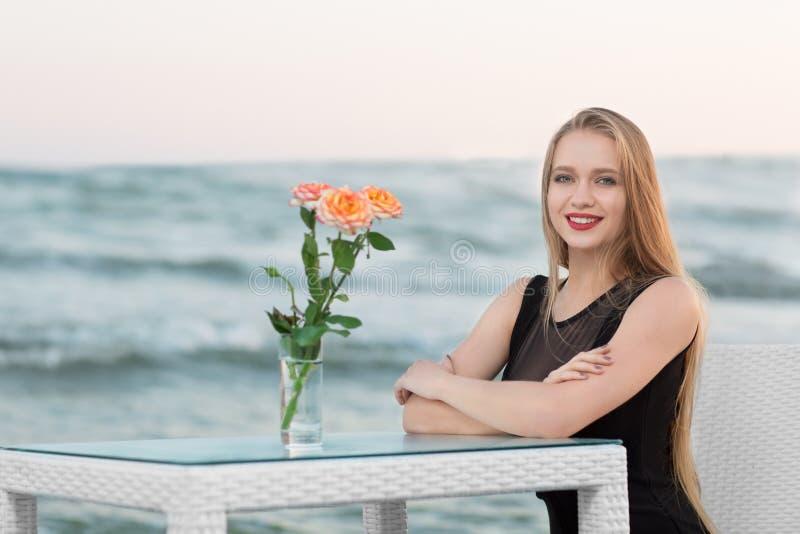 En härlig kvinna nära havet på bakgrund för blå himmel i sommar Den ursnygga stilfulla unga kvinnan vilar nära den blåa lagun royaltyfri bild