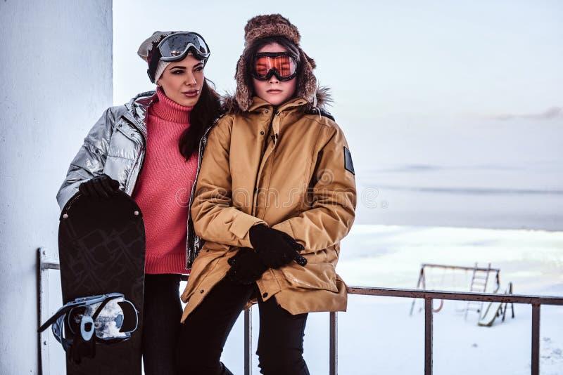 En härlig kvinna och hennes iklädda stilfulla varma kläder för son som står med snowboarden bredvid räcket på det snöig arkivbilder