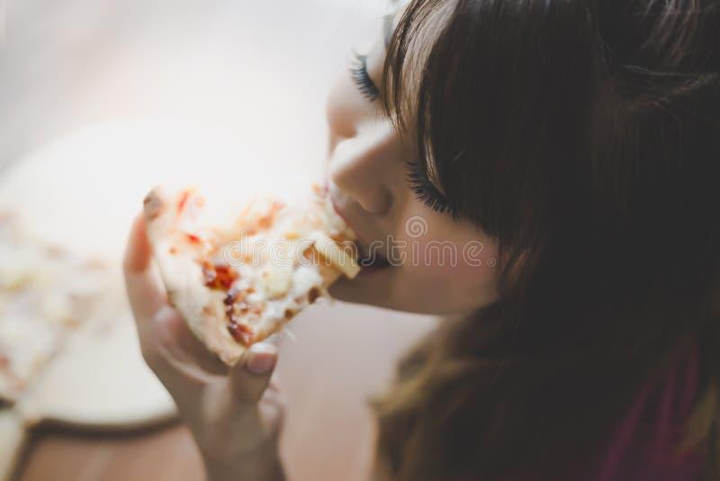 En härlig kvinna rymmer ett stycke av pizza och äter det Den nätta asiatiska flickan känner sig lycklig och tycker om att äta piz royaltyfri fotografi
