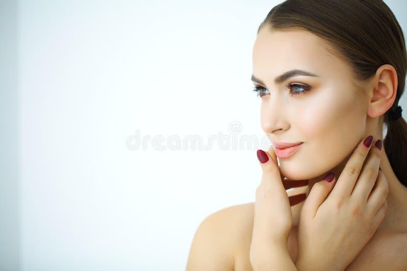 En härlig kvinna som använder en produkt, en fuktighetsbevarande hudkräm eller lotusblommor för hudomsorg royaltyfri foto