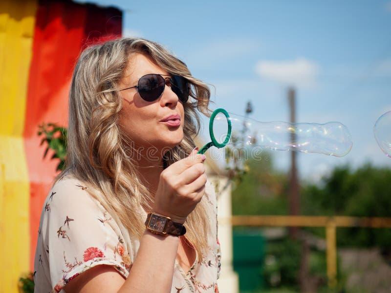 En härlig kvinna som blåser bubblor som tonas med en retro effekt app för tappninginstagramfilter eller handling royaltyfri foto
