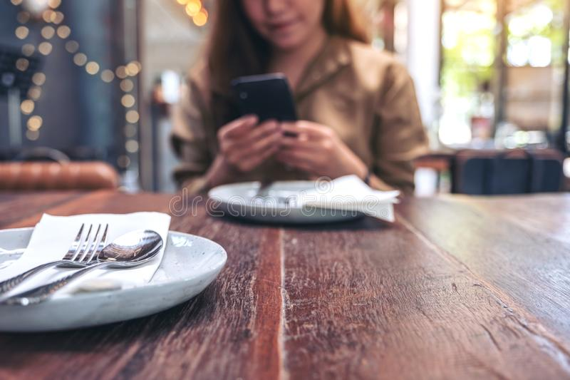 En härlig kvinna som rymmer, använder och ser den smarta telefonen, medan ha ett mål i restaurang arkivbilder
