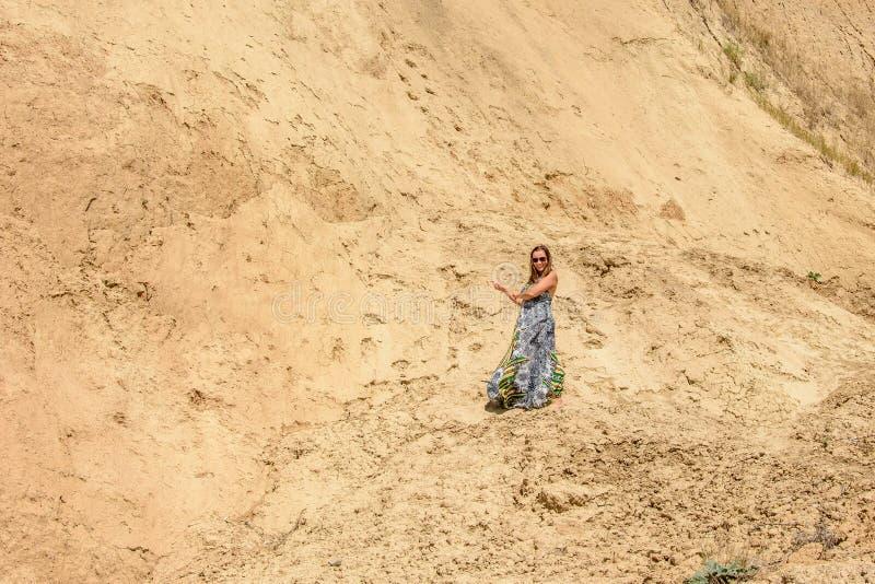 En härlig kvinna står i en klänning och solglasögon mot ett sandigt berg arkivbilder