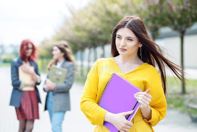 En härlig kvinna står med en mapp Utbildningsbegrepp, examina, kamratskap och grupp m?nniskor royaltyfria foton