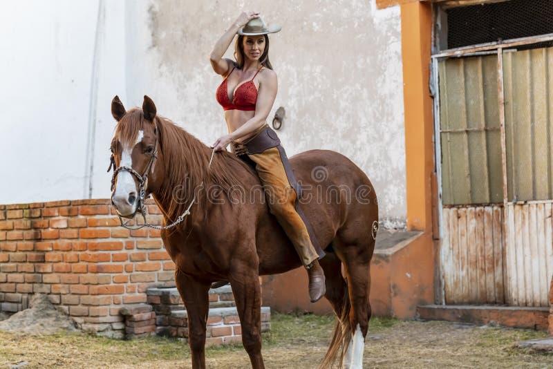 En härlig latinamerikansk brunettmodell Rides en häst på en mexicansk lantgård royaltyfria bilder