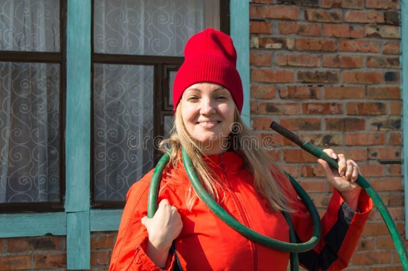 En härlig le bondekvinna som poserar i hennes trädgårds- innehav en bevattna slang, jordbruk och egenföretagande arkivbild