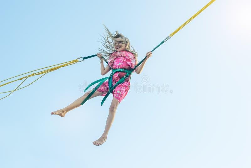 En härlig liten flicka flyger upp på rubber remmar Den stärkande ritten royaltyfri fotografi