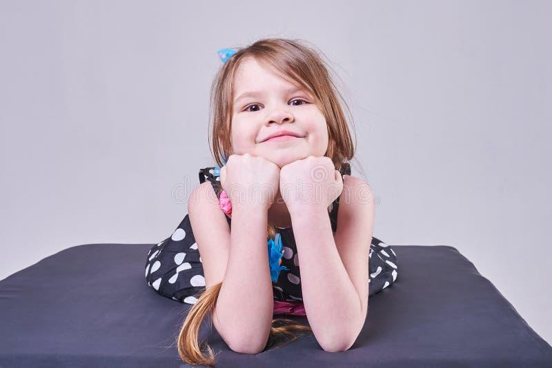 En härlig liten flicka ligger och att rymma hennes huvud med hennes händer och leenden royaltyfri bild