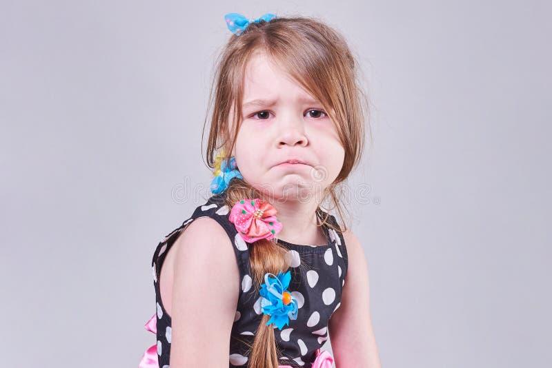 En härlig liten flicka, med ett ledset uttryck av hennes framsida, ska gråta arkivfoton