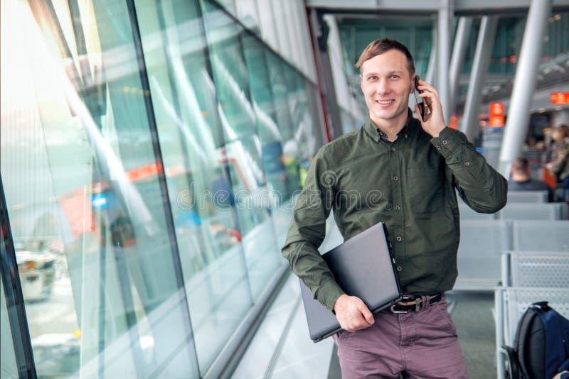 En härlig lycklig grabb med en bärbar dator och en skjorta som talar på telefonen och ler bak fönstret på flygplatsen royaltyfri foto