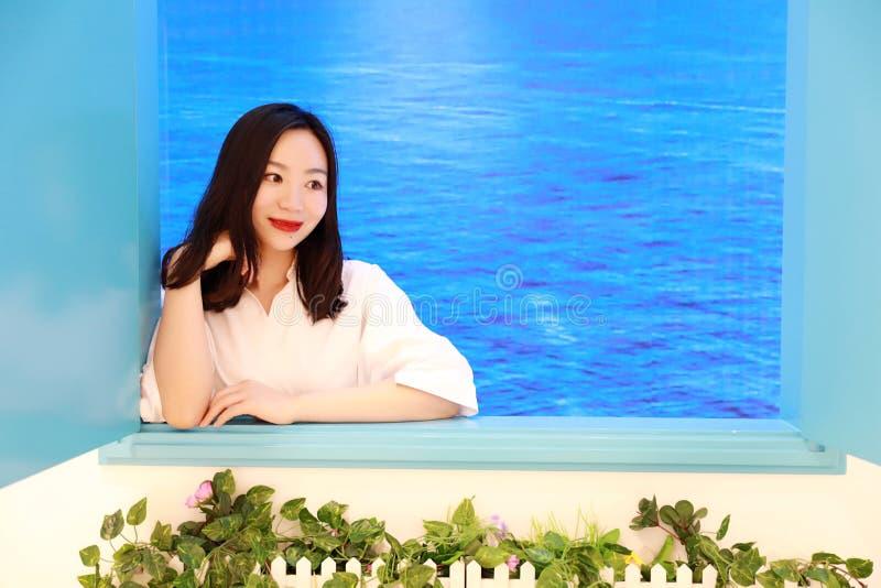 En härlig nätt ung flickakvinnakvinnlig tycker om blick för tid för landskapbotsikt angenäm utanför fönstret på en strand royaltyfri foto