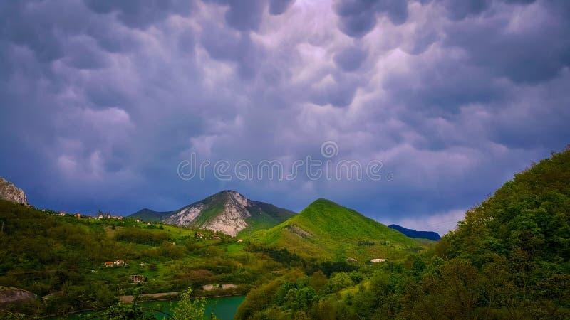 En härlig sikt av bergen och sjön De oerhörda molnen i bakgrunden arkivfoton