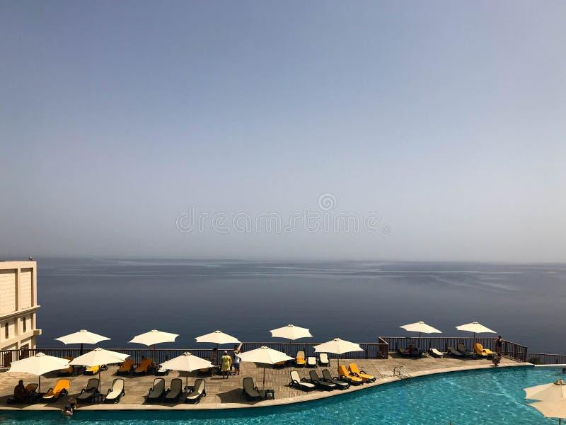 En härlig simbassäng med klart vatten med solparaplyer från solen i ett hotell i en tropisk exotisk semesterort, en brunnsort på  arkivfoton