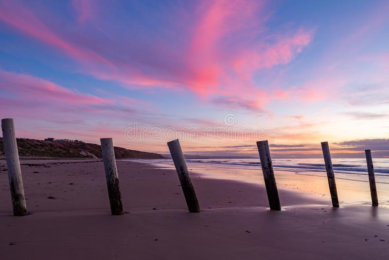 En härlig solnedgång på moanastranden med trästolpeseperatien arkivbilder