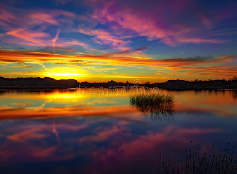 En härlig solnedgång på en stillhet och en fridsam sjö - färgrik himmel royaltyfria foton