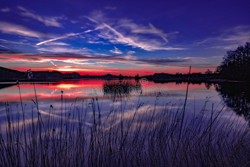 En härlig solnedgång på en stillhet och en fridsam sjö - färgrik himmel royaltyfri bild