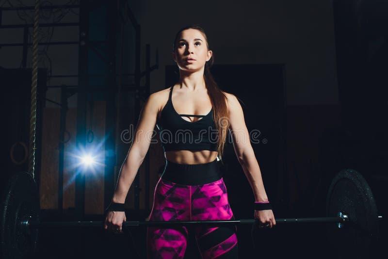 En härlig sportflicka utbildar en bicep med en stång i hennes händer i idrottshallen royaltyfri foto