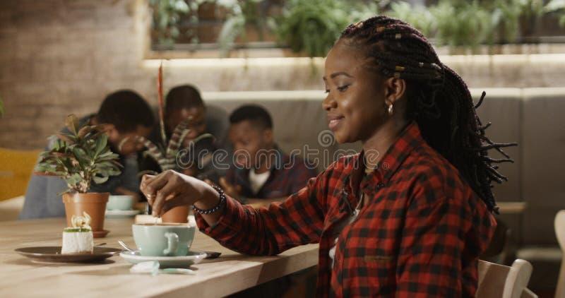 En härlig svart flicka häller socker in i kaffe royaltyfri fotografi