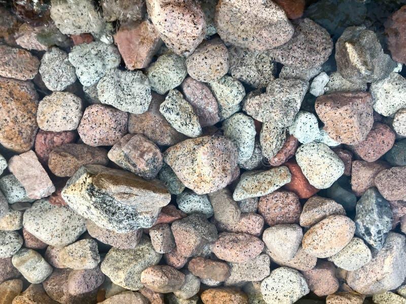 En härlig textur av denfärgade rundan och ovala naturliga fasta stenstenar, stenblock, kullersten under det blåa vattnet, under royaltyfri bild