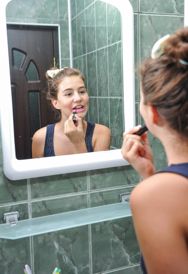En härlig tonårig flicka som sätter läppstift och kontrollerar, om hon ser fint arkivbilder