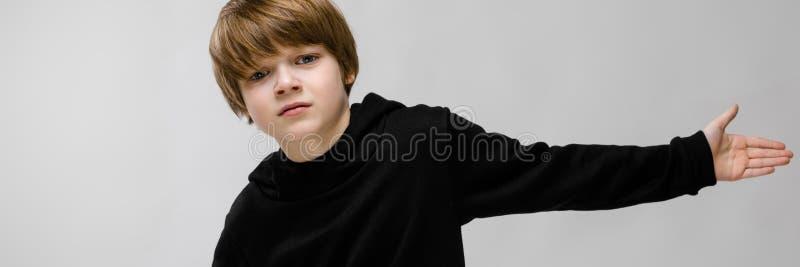 En härlig tonåring i en svart tröja och ljusjeans Pojkespridningen hans händer i båda riktningar fotografering för bildbyråer