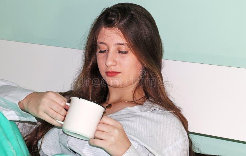 En härlig tonårs- flicka dricker kaffe royaltyfria foton