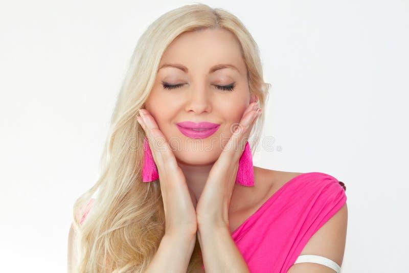 En härlig ung blondin med stängda ögon och ett leende, rymmer händer vid framsidan Sinnesrörelser av salighet och nöje royaltyfri fotografi