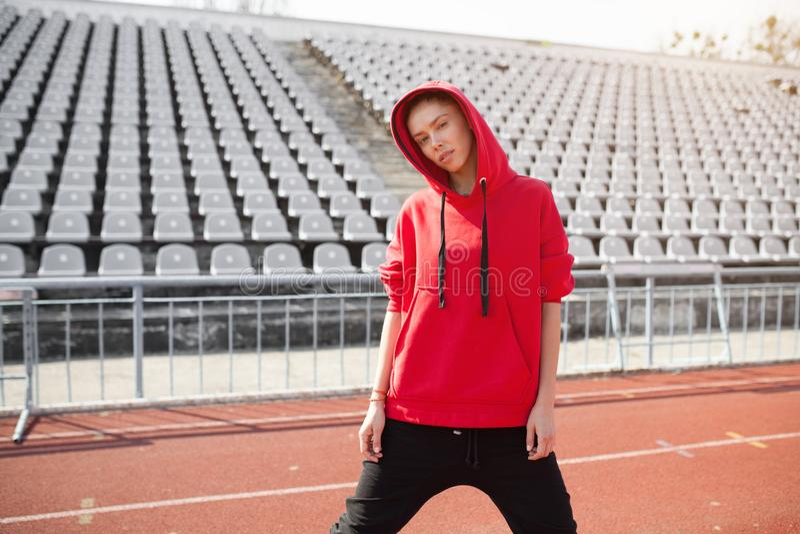 En härlig ung flicka av ställningar för blandat lopp på ett iklätt rinnande spår för sportstadion en röd hoodie med en huv royaltyfri fotografi