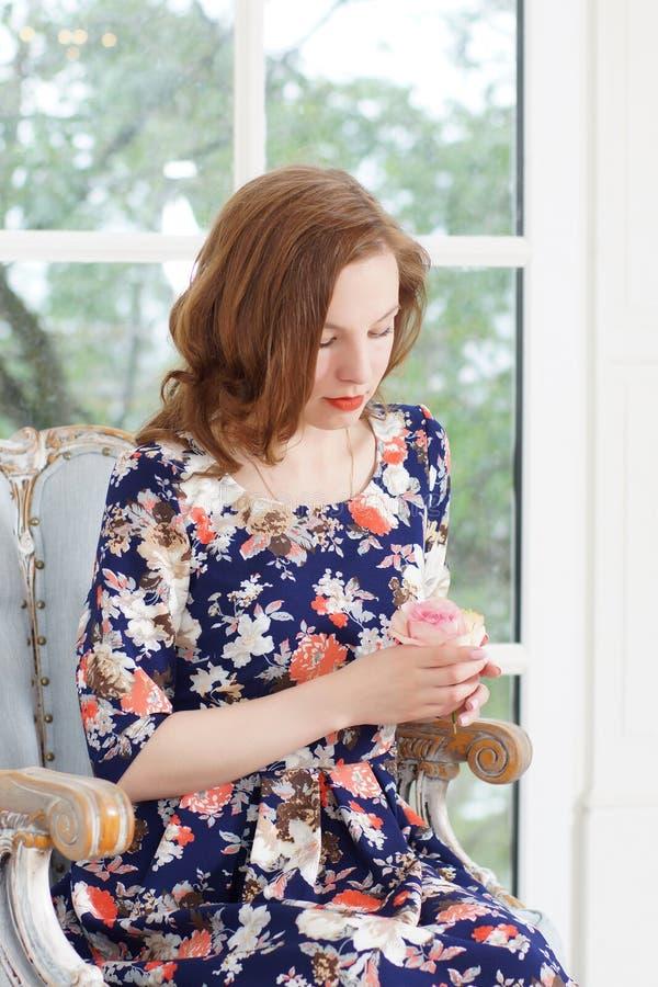 En härlig ung flicka i en ljus färgrik klänning sitter i en fåtölj vid fönstret och ser hänsynsfullt på rosen fotografering för bildbyråer