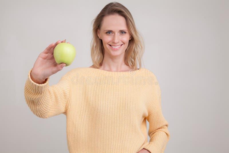 En härlig ung flicka med blont hår ler på kameran och sträcker ett grönt äpple till kameran hon ?r ikl?dd en guling royaltyfria foton