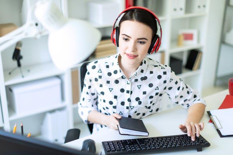 En härlig ung flicka sitter i hörlurar på en tabell i kontoret, rymmer en anteckningsbok i hennes hand och skriver på texten royaltyfria foton