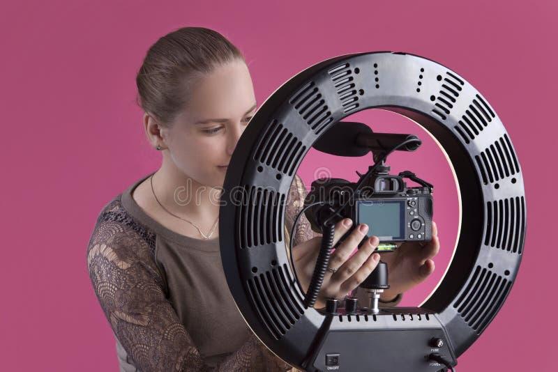 En härlig ung flickablogger ställer in kameran i hållaren arkivfoto