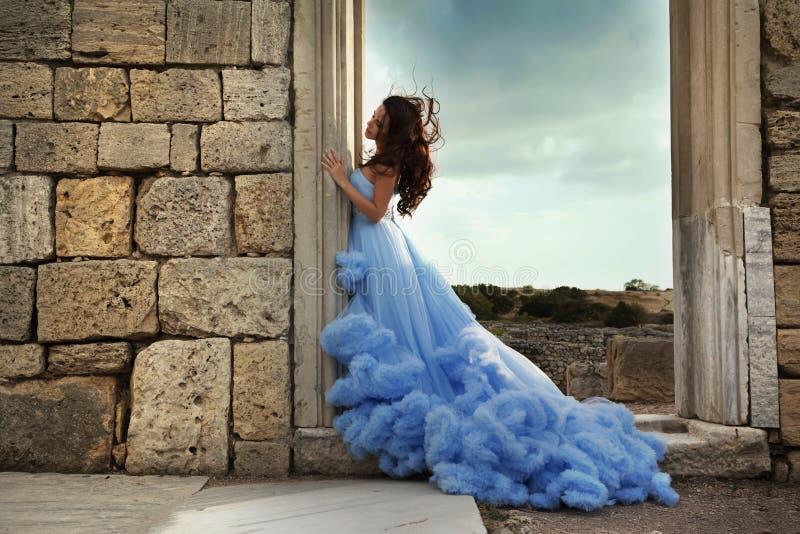 En härlig ung kvinna i en blå klänning står bredvid forntida fördärvar royaltyfri bild