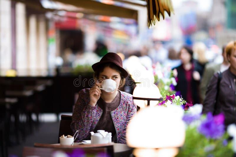 En härlig ung kvinna i en hatt sitter på en terrass i ett kafé, dricker te och håller ögonen på att förbigå för folk arkivbild