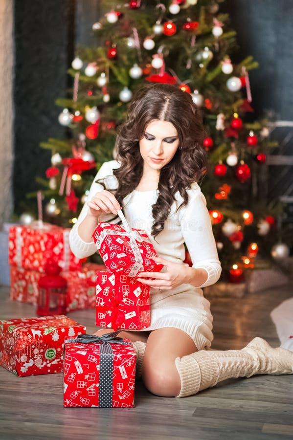 En härlig ung kvinna i en vit tröjaklänning packar upp gåvor för ` s för nytt år mot bakgrunden av ett träd för nytt år Brunett i royaltyfria foton
