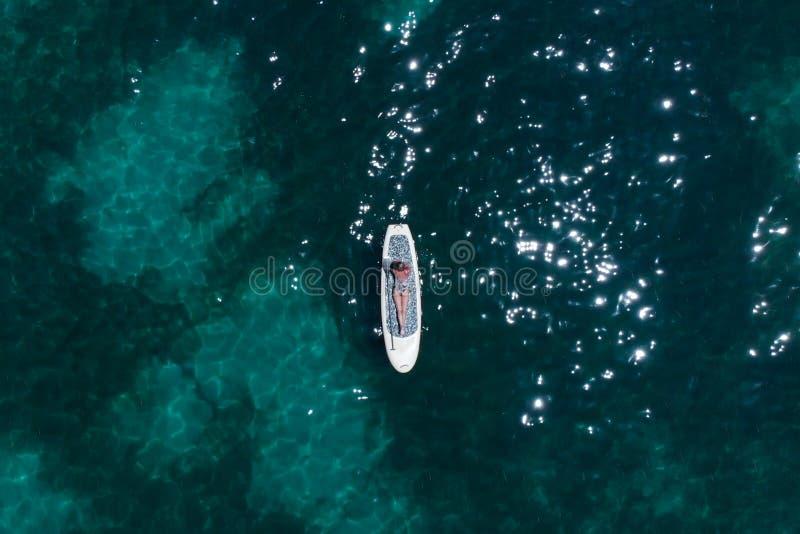 En härlig ung kvinna kopplar av på ett SUPbräde i havet nära ön Surrskott arkivbild