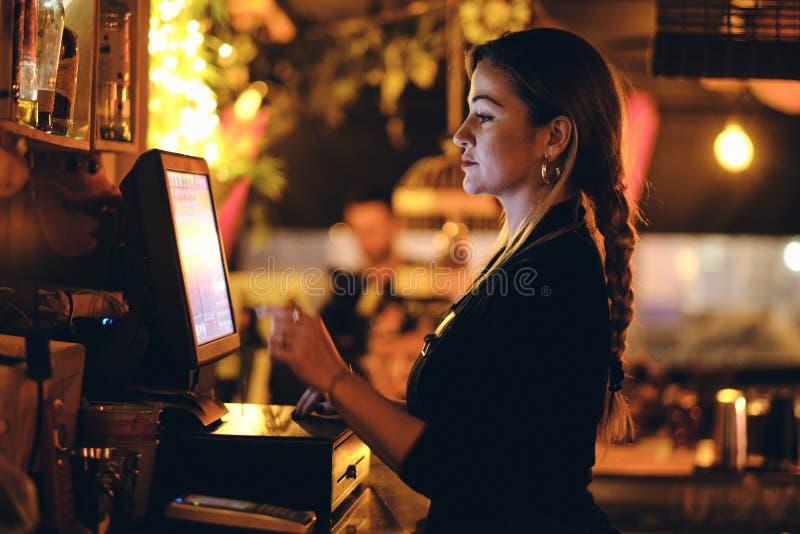 En härlig ung kvinna på skrivbordet i en restaurang royaltyfri foto