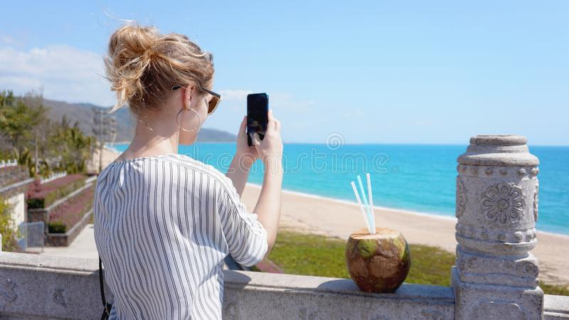 En härlig ung kvinna på en tropisk strand med en telefon i hennes händer royaltyfria bilder
