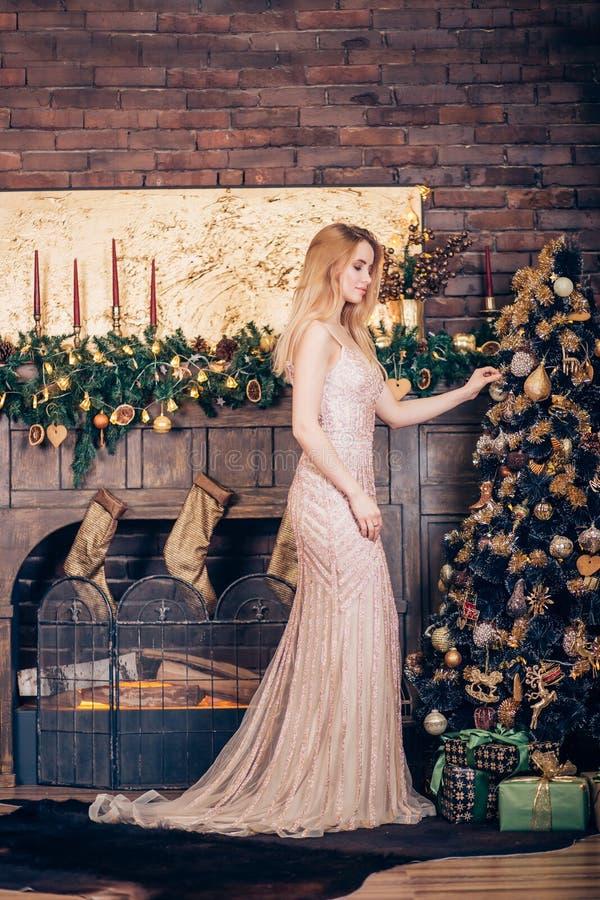 En härlig ung kvinna som bär en lång guld- klänning, smyckar julgranen med leksaker och bollar i huset nära spisen royaltyfria foton