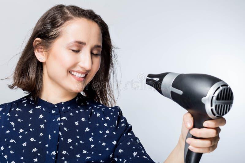 En härlig ung kvinna som känner sig lycklig, medan genom att använda en hårtork och en hårborste fotografering för bildbyråer