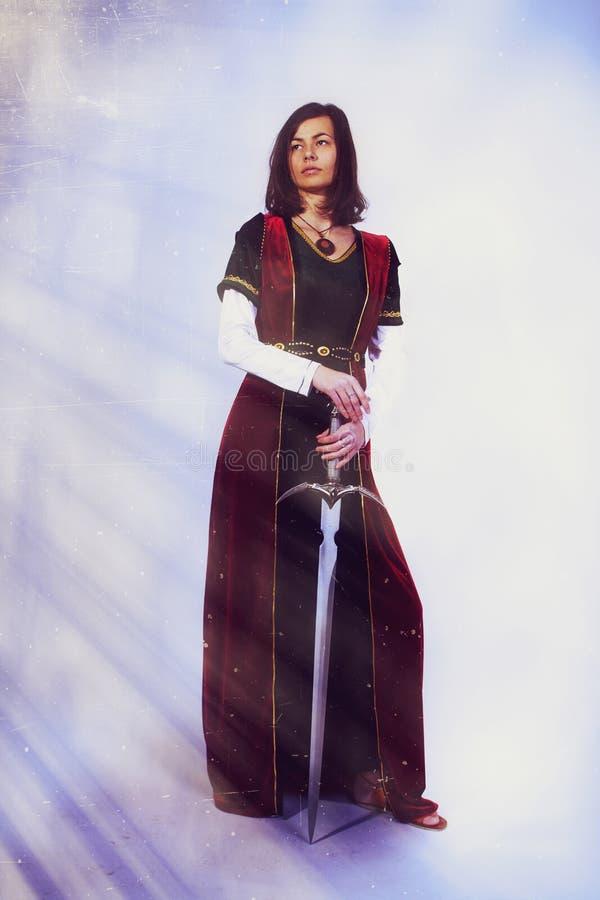 En härlig ung kvinna som poserar i historisk klänning royaltyfri foto
