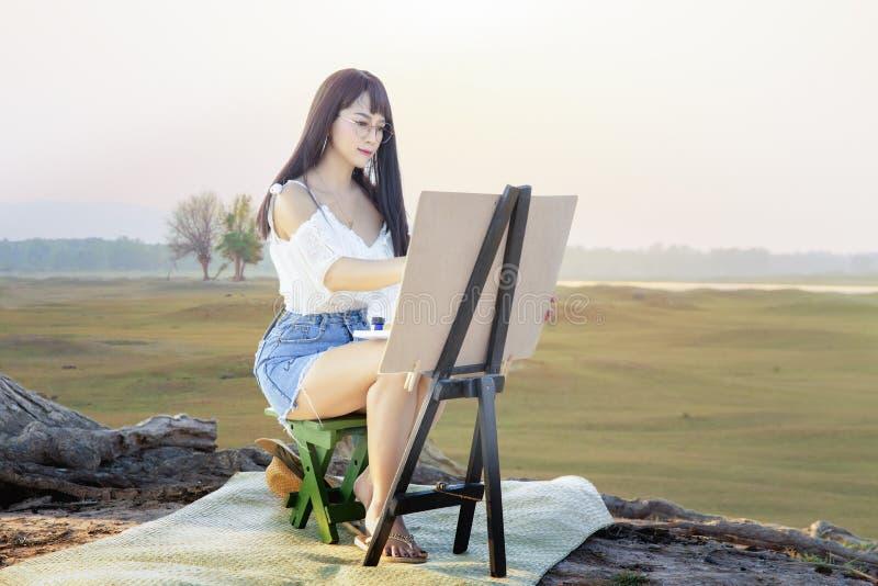 En härlig ung kvinna som sitter i en äng royaltyfri bild