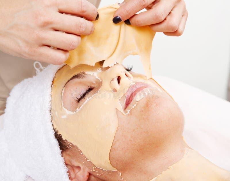 En härlig ung kvinna tar bort den ansikts- maskeringen i en skönhetmitt arkivfoton
