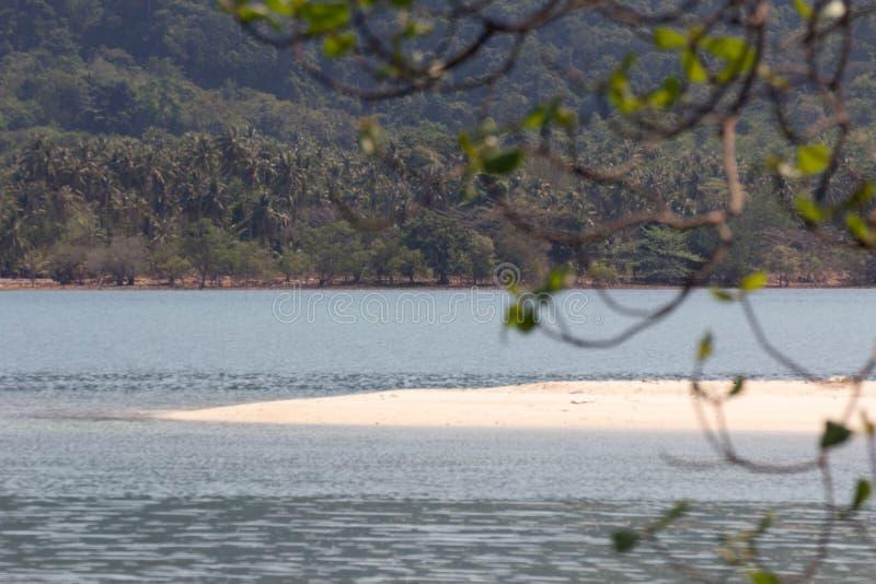 En härlig vit tropisk sandig strand som omges av ett blått hav arkivfoton